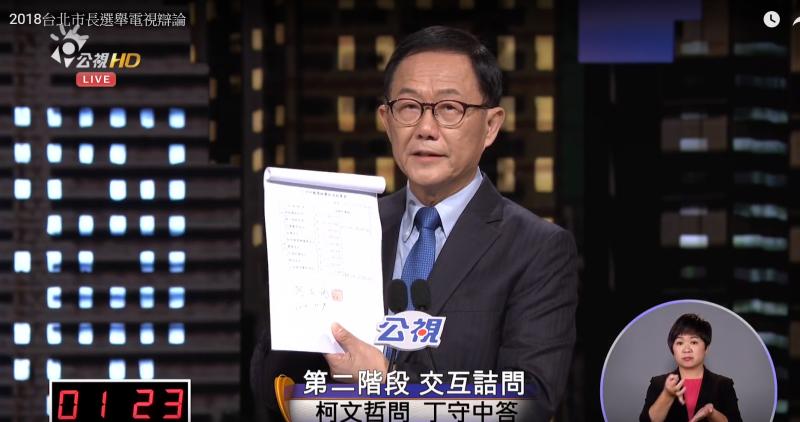 20181110-由公視舉辦台北市長電視辯論10日登場,台北市長柯文哲進行第二階段交叉詢問時,針對藍綠兩黨候選人提出公布競選經費要求。國民黨候選人丁守中拿出數據,公布自己競選經費收支。(取自YouTube)