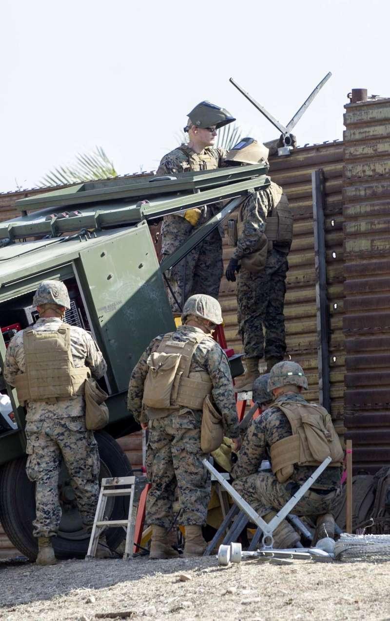 美國海軍陸戰隊的士兵正在邊境的圍牆上佈署蛇籠網。(美聯社)