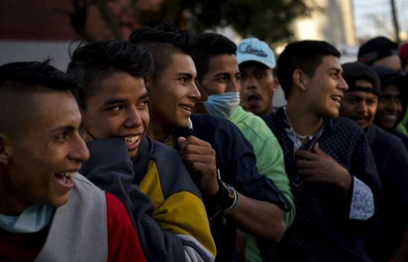 11月23日,許多中美洲移民在墨西哥提華納市庇護所等待領取食物(美聯社)