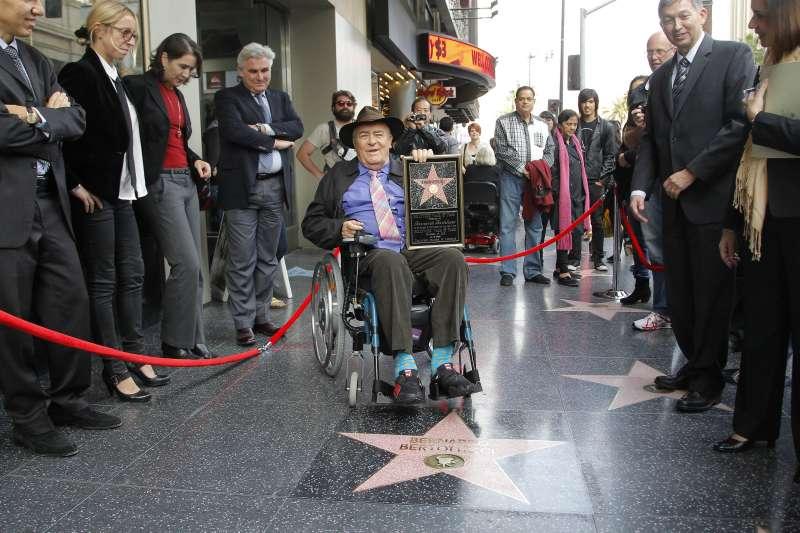 2013年,貝托魯奇造訪美國加州洛杉磯好萊塢星光大道,舉著自己的名人星章(美聯社)