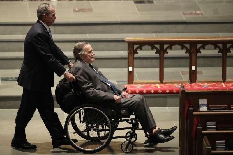 2018年4月21日,小布希推著老布希的輪椅,參加母親芭芭拉的葬禮(AP)