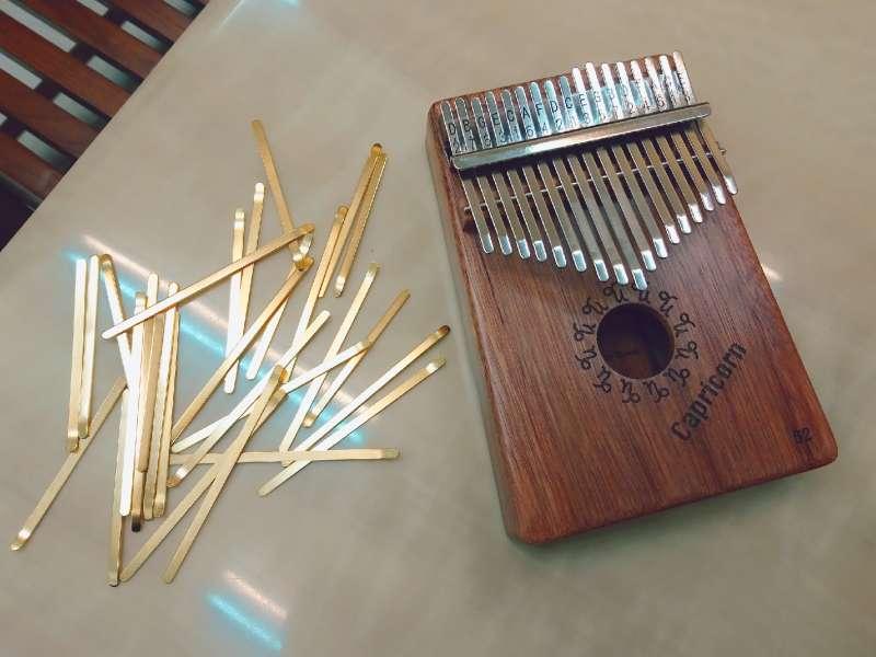 就像在兒童小提琴的琴弦上綁緞帶、做記號一樣,卡林巴琴也有可愛的小音貼,貼上後就能清楚辨識音階,稍微熟悉一下左右手的配合度,就能撥奏出簡單的旋律了。旁邊散落的是另一種金色琴片,鄭啟富笑說裝著金色琴片的卡林巴琴已經賣到缺貨了。(圖/王芸軒攝)