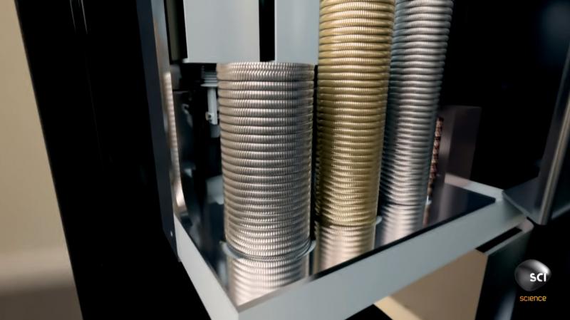 硬幣整齊堆疊在儲存槽內,當需要找零時,便會開啟下方機關,一枚枚地進行退幣。(圖/截自YouTube)