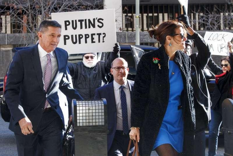 佛林與身旁的抗議標語:「川普養的狗」。(美聯社)