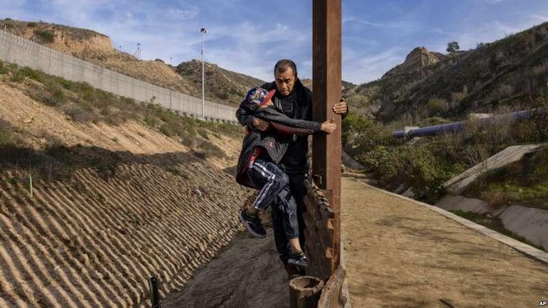 一位宏都拉斯人帶兒子在加州美墨邊界從墨西哥一側翻越圍牆。(美聯社)