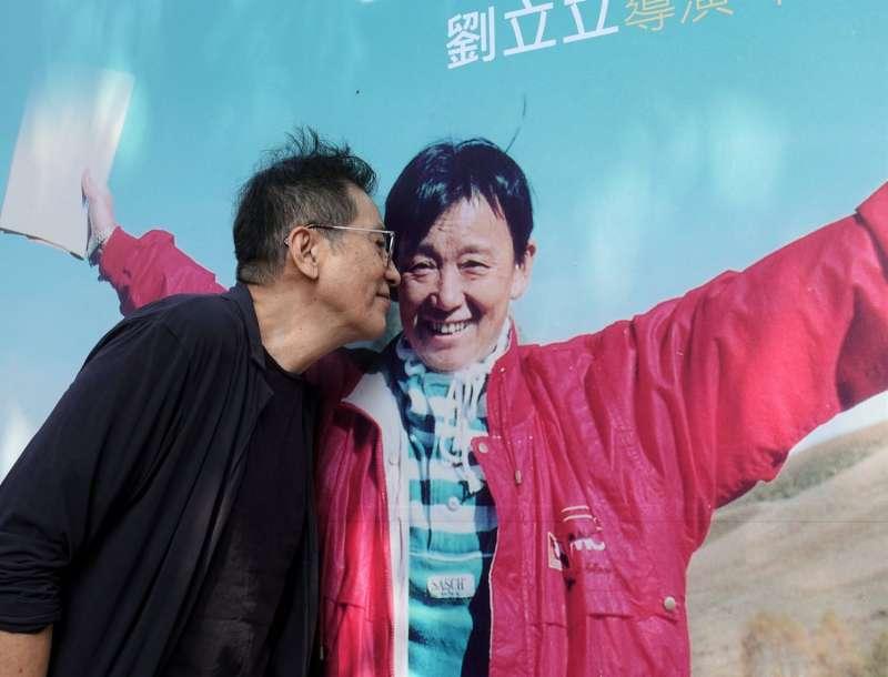 劉立立的家屬在台北華山文創園區舉辦紀念回顧展,資深影星秦漢(黑衣)親臨現場追憶劉立立點滴,並輕吻劉立立人物看板,也對著看板上的劉立立照片說:「她的笑容永遠這麼開朗。」(圖/文化+)