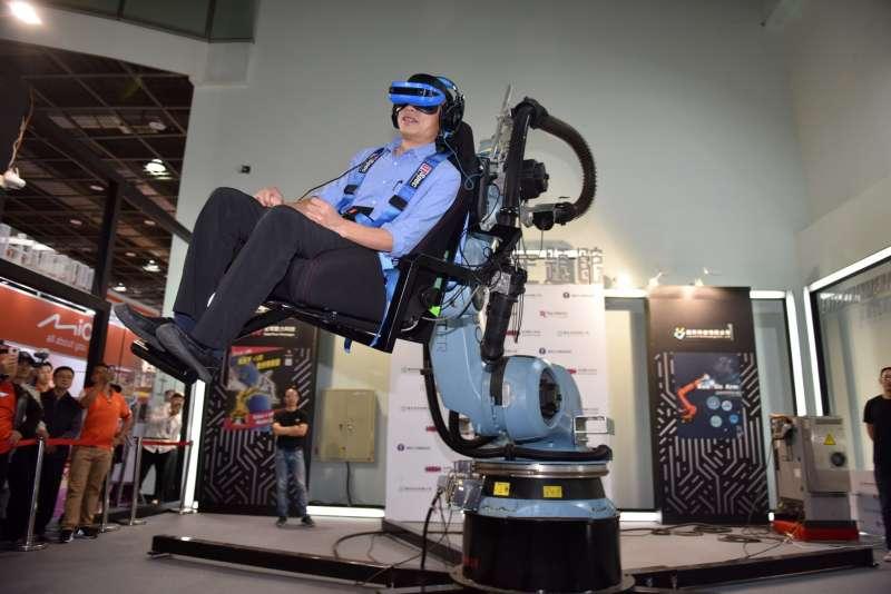 高雄市長韓國瑜在會場主題館親身體驗巨型機械手臂VR模擬器,感受身歷其境的震撼。(圖/徐炳文攝)
