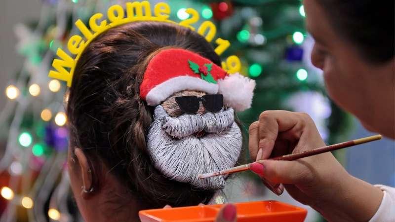 印度艾哈邁達巴德,一名化妝師在新年晚會前幫忙裝飾頭髮。(圖/BBC中文網)
