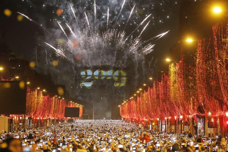 法國巴黎凱旋門前,大批民眾聚集共同迎接2019年新年到來,一起觀賞美麗煙火(美聯社)