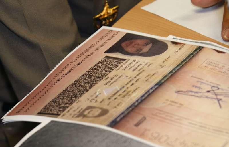 泰國移民署警長蘇拉察特向媒體說明時,桌上擺著奎農護照複本(美聯社)