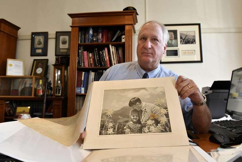 拍賣行 Alexander Historical Auctions 創辦人 Basil Panagopulos 展示最近成交的宣傳照,圖中希特拉擁抱一名猶太裔德國女孩。(圖片由*CUP提供)