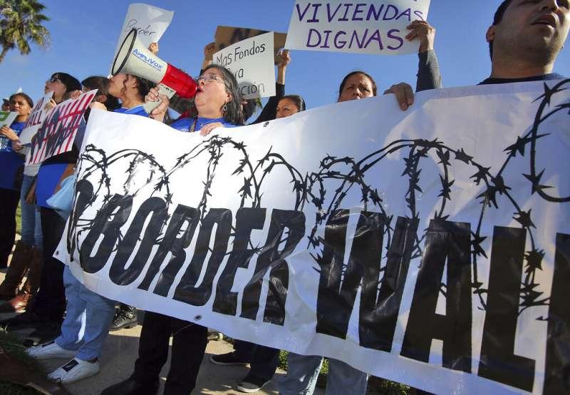 2019年1月10日,川普到德州視察美墨邊境,反對蓋牆的民眾舉布條抗議。(AP)
