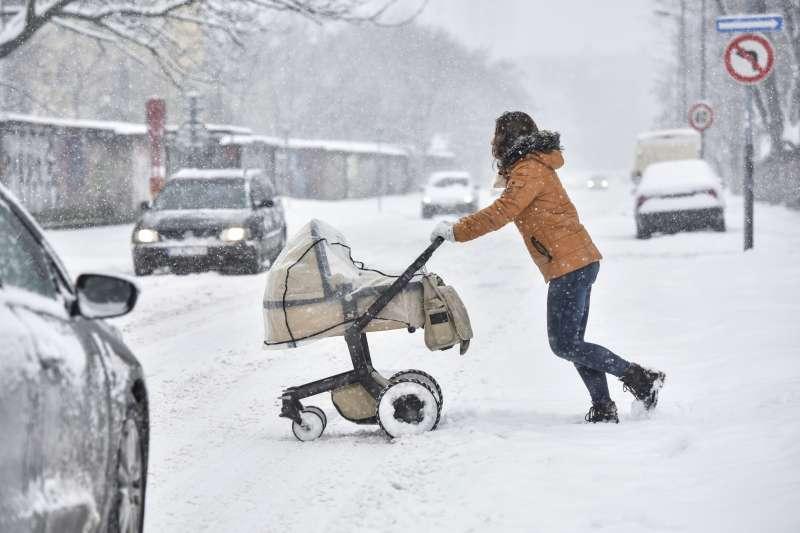 中歐斯洛伐克大雪,一名婦女8日推著嬰兒車通過積雪的馬路(美聯社)