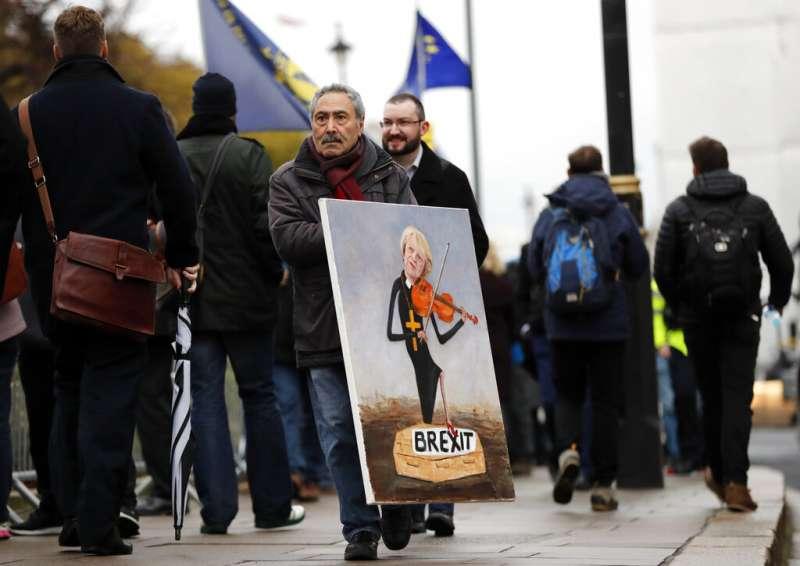 英國民眾拿著梅伊拉小提琴的肖像,不過她腳下踩的竟是名為「英國脫歐」的一具棺材。(美聯社)