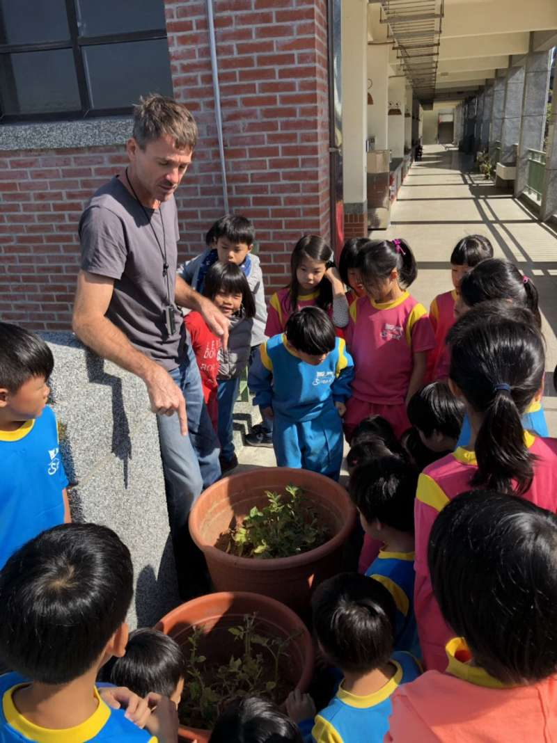 小朋友與外籍教師Erick熱烈討論番茄生長的問題。(黃博郎攝)