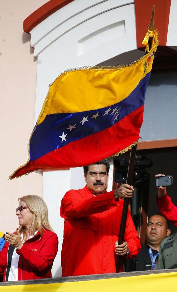 委內瑞拉總統馬杜洛在總統府陽台揮舞國旗,在美國不承認的逆境下猶做困獸之鬥。(美聯社)