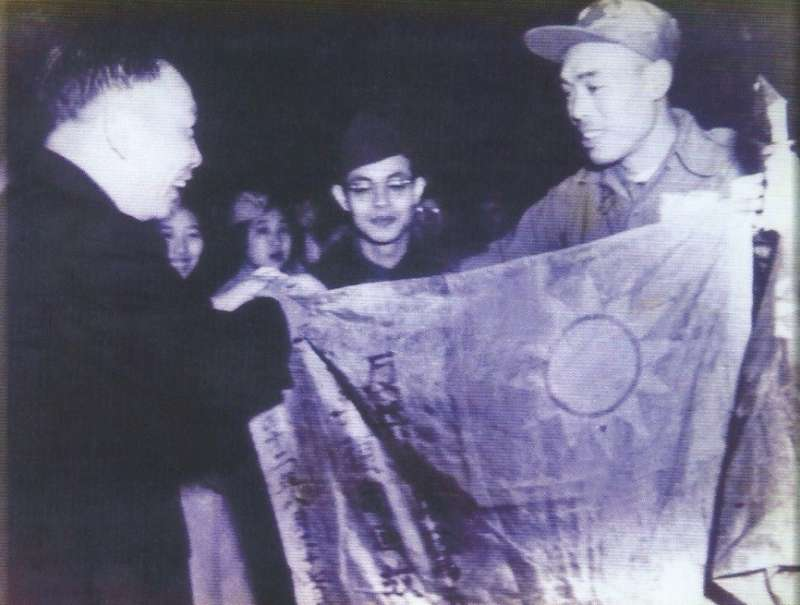 1954年(民國43年)1月,義士代表將他們在濟州島戰俘營以鮮血染成的中華民國國旗,獻給時任國防會議副秘書長蔣經國先生,圖片來源:《抉擇──一萬四千名反共義士(輔導會/103.01.23出版/勒巴克顧問公司承印)》,作者賈忠偉提供