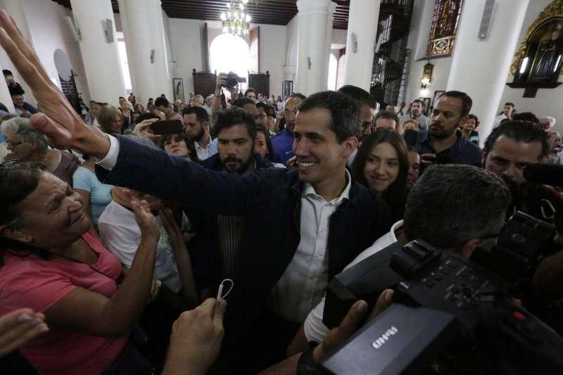 瓜伊多27日出席彌撒時遭支持者簇擁。(美聯社)