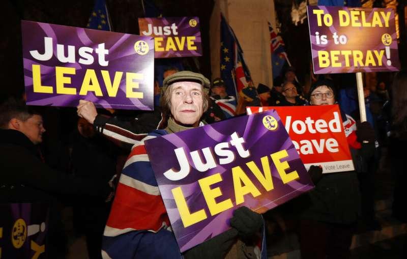 英國脫歐支持者在國會外舉牌抗議。(AP)