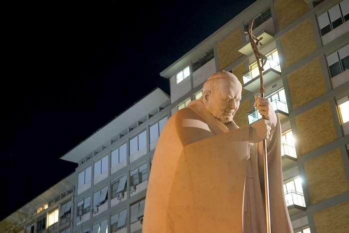 教宗若望保祿二世雕像(後方五扇灰色窗為教宗病房)。(曾廣儀攝)