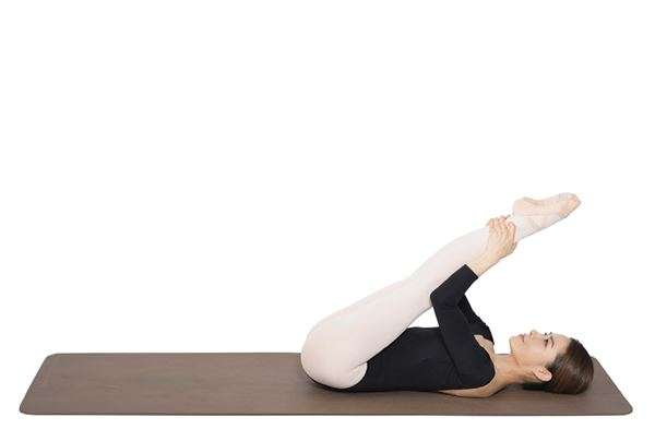 動作6:一邊吐氣,將膝蓋伸直,一邊用手抓著兩腳腳踝往身體方向拉近。(圖/華人健康網提供)