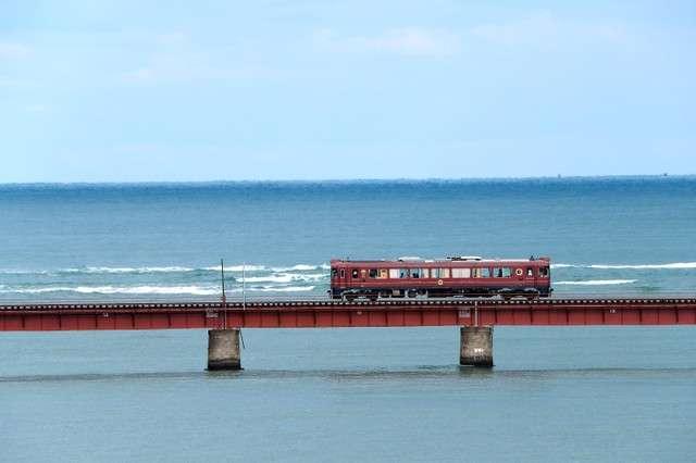 以海為背景,行駛於由良川橋梁的丹後赤松號。(圖/潮日本)