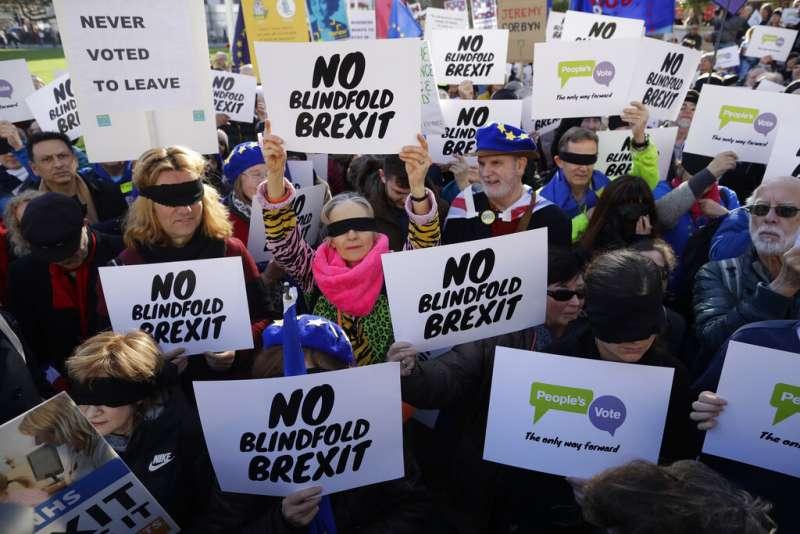 留歐派支持者矇住雙眼,高舉「不要盲目脫歐」的標語與布條。(美聯社)