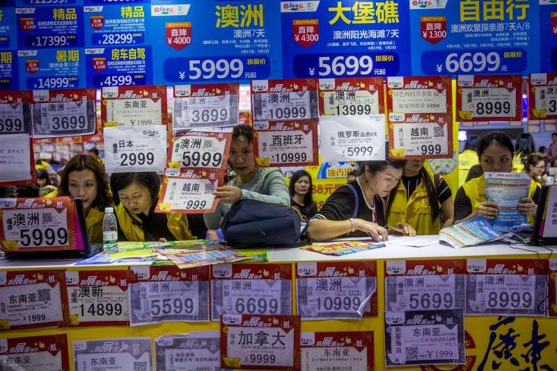 中國國際旅展期間,人民查看旅行優惠,卻有1750萬人因信用不良無法出國。(AP)