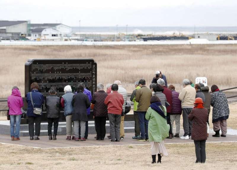 福島縣居民11日在311日本大地震的慰靈碑前哀悼。(美聯社)