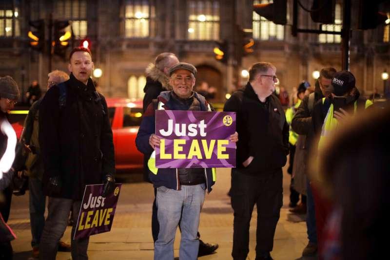 反對推遲脫歐的英國民眾在倫敦街頭高舉標語:趕快脫了吧!(美聯社)