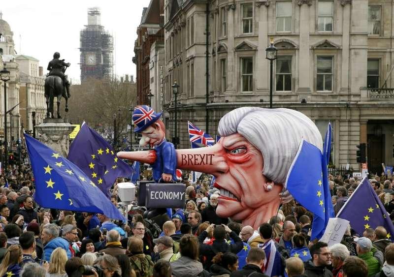 反脫歐的英國民眾23日在倫敦遊行,首相梅伊成了醜怪的長鼻子女人。(美聯社)