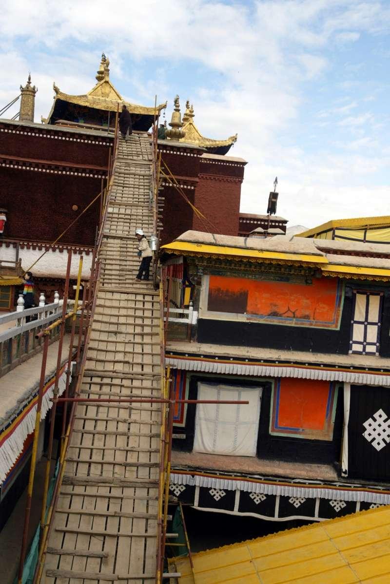 幾名工人在西藏布達拉宮頂部施工。(新華社)