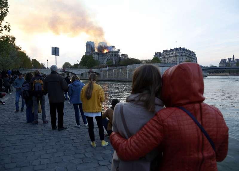 巴黎民眾震驚地看著聖母院大教堂被大火吞噬(美聯社)
