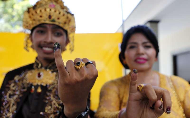 印尼選民投完票後,自豪地展示蘸了投票墨水的紫色手指(美聯社)