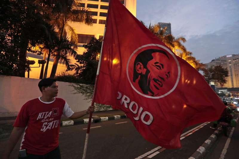 現任總統佐科威支持者17日在街上揮舞印著佐科威頭像的旗幟(美聯社)
