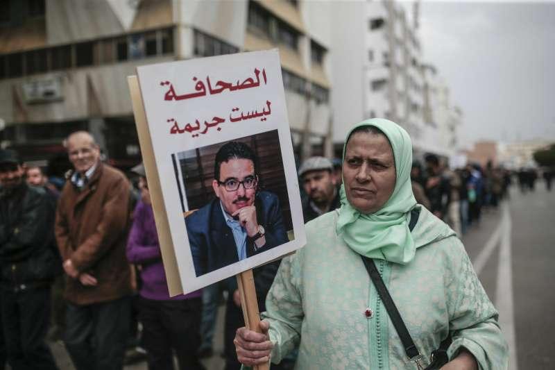2019年4月21日,摩洛哥首都拉巴特街頭爆發示威,民眾手舉記者伯敻的肖像,標語上寫著:「新聞工作不是犯罪」。(AP)