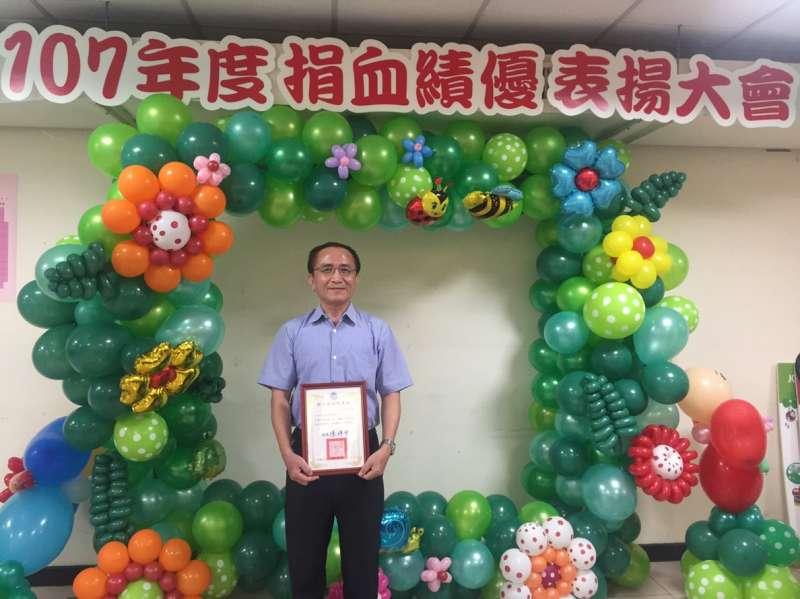 由事業部行政室主任陳良安在國立高雄師範大學接受褒揚。(圖/徐炳文攝)