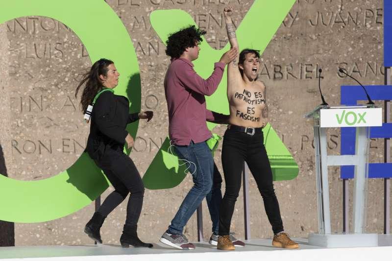 西班牙大選4月28日登場,一名女子在極右派政黨「聲音黨」的造勢場合上空抗議。(AP)