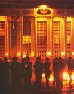 六四天安門 6月4日凌晨4時後,部隊開始於天安門廣場執行清場指示,可以看見背景處的人民大會堂以及地上的燃燒物。(維基百科)