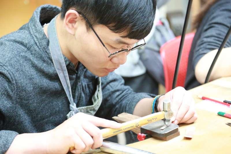 青年參加台中市就業服務處舉辦的「解密百業,實境體驗」活動,嘗試製作精細金工藝品。(圖/臺中市就業服務處提供)