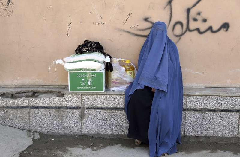 一名阿富汗穆斯林女性與她所獲得的物資,在齋戒月期間,許多穆斯林會行善幫助需要的人。(AP)