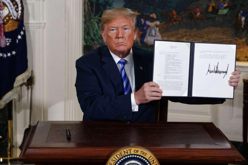 美國總統川普2018年5月8日對媒體展示美國退出伊朗核協議的文件。(美聯社)