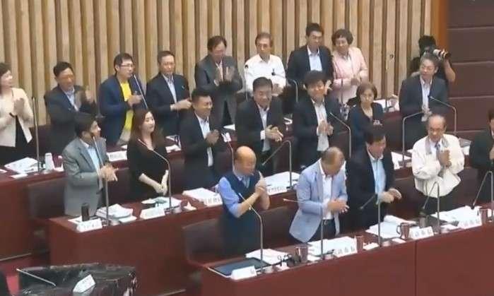 20190514-國民黨高雄市議員王義雄質詢時,要求所有局處首長起立為高雄市長韓國瑜鼓掌,讓官員們各個表情錯愕。(截圖自高雄市議會)