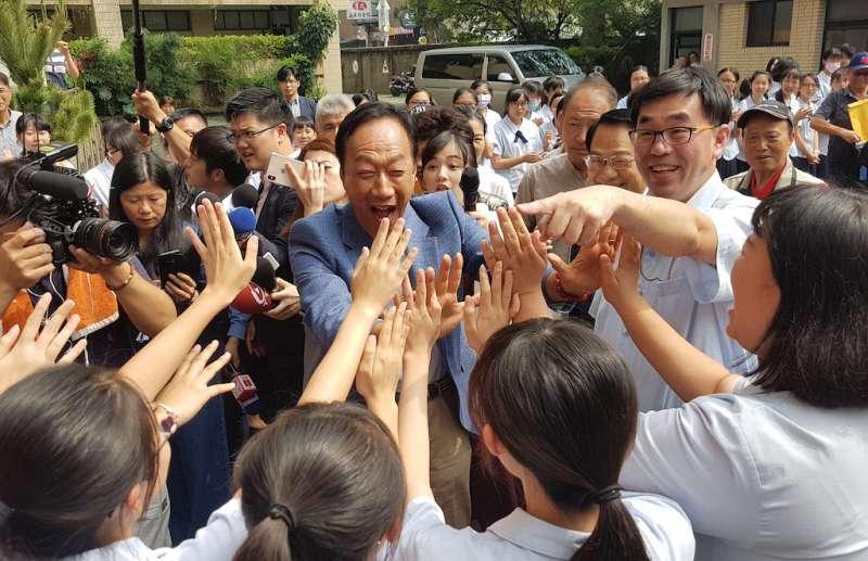 郭台銘走進新竹市私立曙光女中,立即受到女同學們列隊擊掌的熱情歡迎。(圖/方詠騰攝)