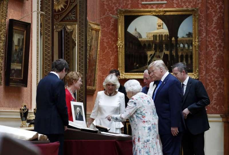 英國女王(中)帶領川普(右二)參觀白金漢宮「影像畫廊」的展覽(美聯社)