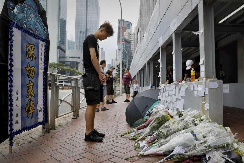 2019年6月15日,一名身穿雨衣的反送中示威者在金鐘太古廣場懸掛橫幅,要求香港政府全面撤回《逃犯條例》,不幸墜樓身亡,許多民眾至事發現場獻花悼念。(AP)