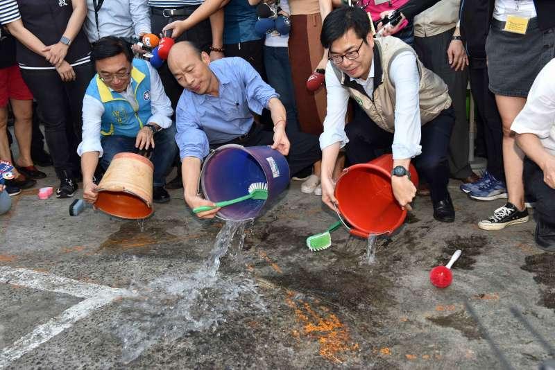 20190619_韓國瑜(中)和陳其邁(右)視察市場環境,了解攤商收攤後對營業用水桶都採取登革熱防疫措施「巡、倒、清、刷」,兩人示範作法。(高雄市政府提供)