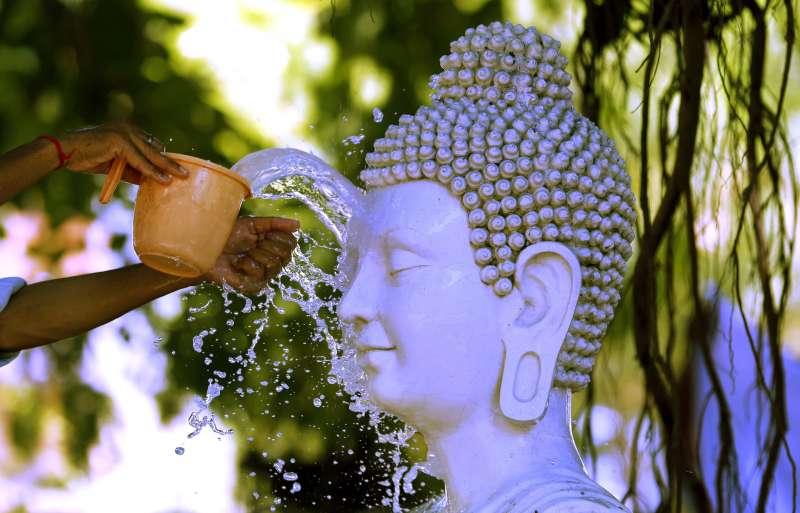 6月14日,印度北方邦安拉阿巴德,一位民眾為佛像淋水。印度今年的雨季遲來,導致該國迎來有紀錄以來史上第二長的熱浪紀錄(美聯社)