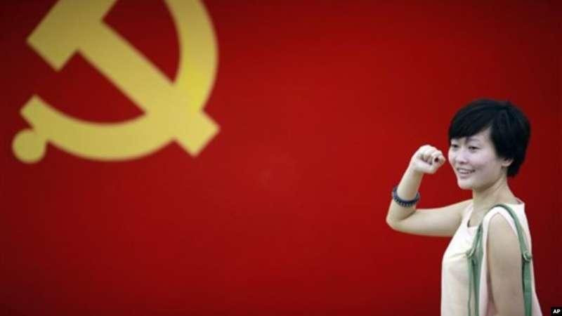 在上海的中共第一次代表大會會址,一名女子在中國共產黨黨旗下擺出宣誓姿勢。(美聯社)