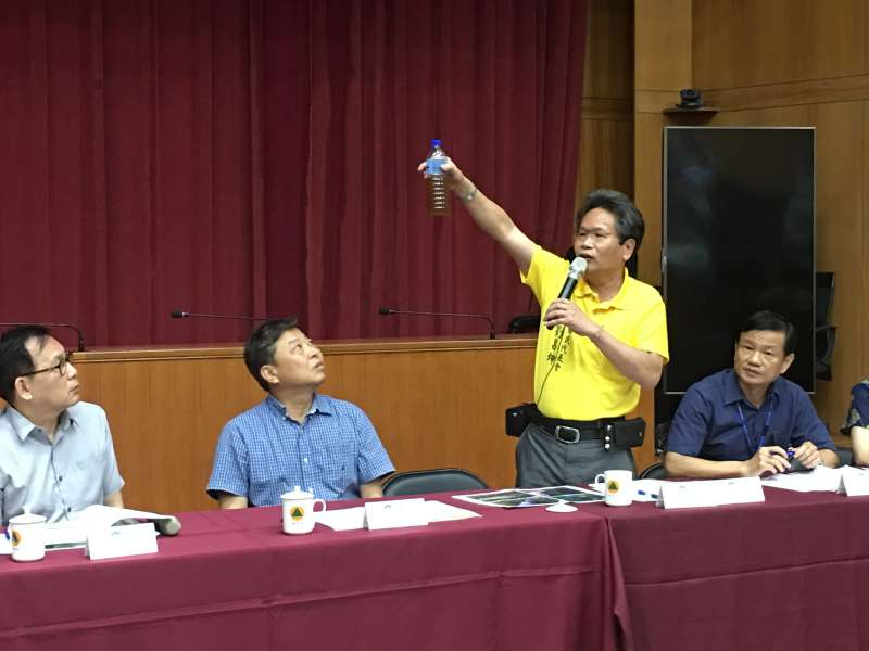 國姓鄉代劉昌坤拿出北港村有機肥料工廠排放的廢水,要縣府的與會官員聞一聞惡臭的味道。(圖/王秀禾攝)